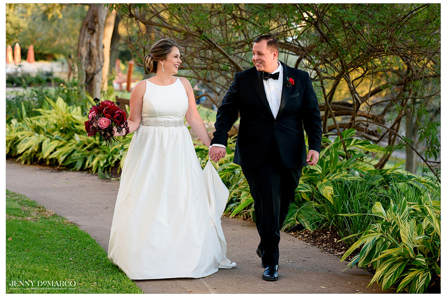 The bride and groom hold hands and walk to the wedding in their wedding attire.