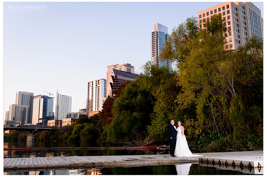 The happy couple smiles on a beautiful Austin day on the lake, surrounded by the buildings.