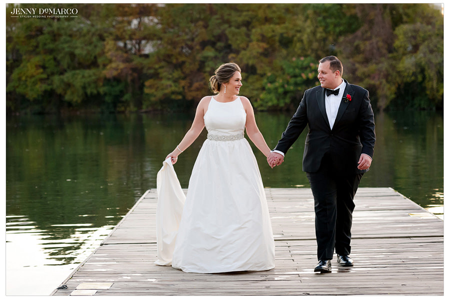 The bride and groom hold hands as they walk along the lake.