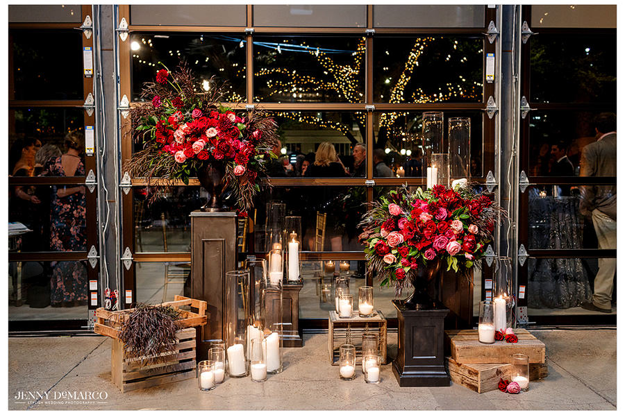 Candles and flowers in shades of red are framed by the night sky coming through the gold window frame.