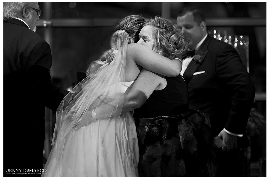 The bride hugs her mom in a sweet black and white moment.