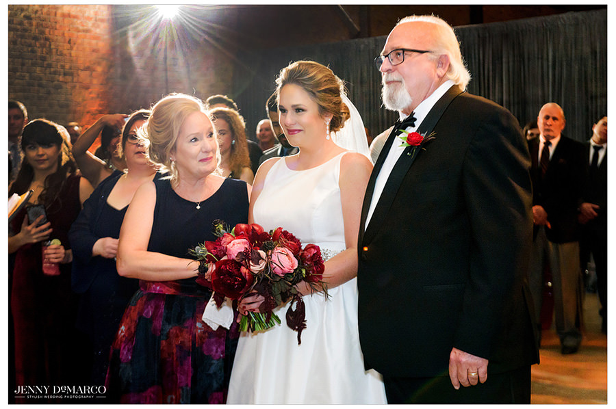 The bride stands alongside her parents as they listen to the speeches from the wedding party.