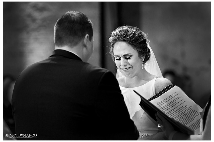 A black and white image of the bride crying as the groom professes his love for her.