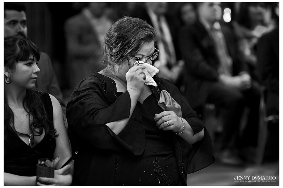 A black and white image of a wedding guest crying at the ceremony.