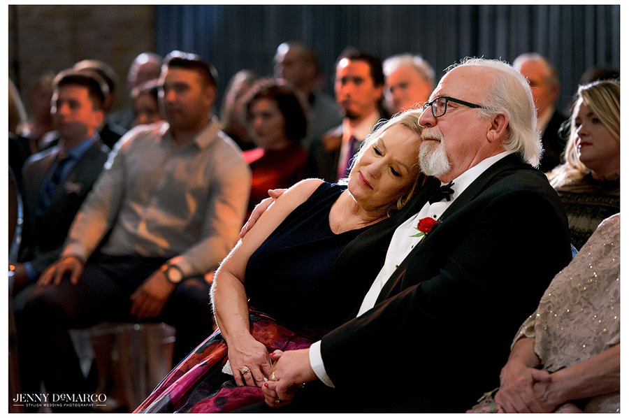 The bride's mom lays on her husband's shoulder as they gaze upon their happy daughter getting married.