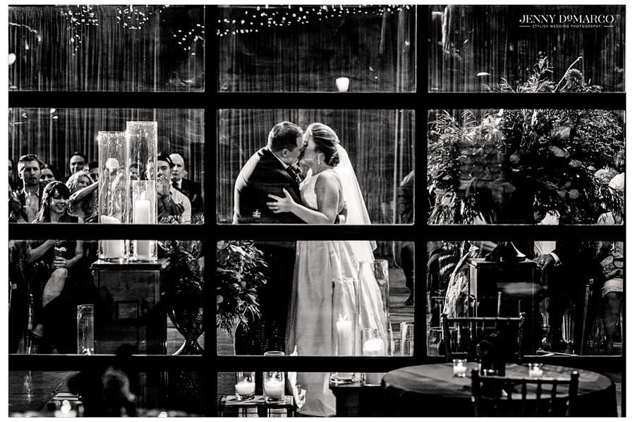 A black and white photo of the bride and groom kissing shot through the window.