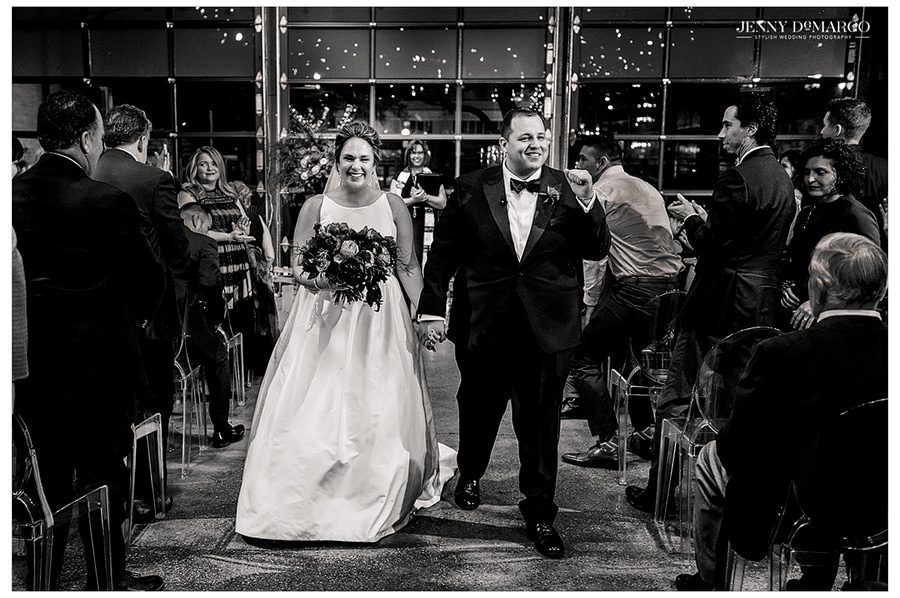 A black and white image of the newlyweds walking down the aisle.