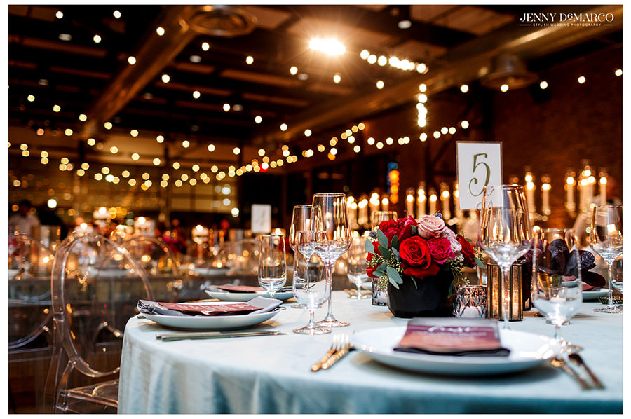 A photo from the reception to highlight the intricate lighting and classic table settings