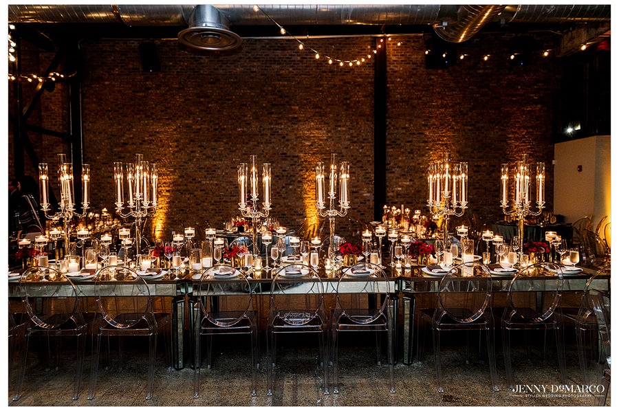 Image of a table setting accented by different candle heights and dark tones.