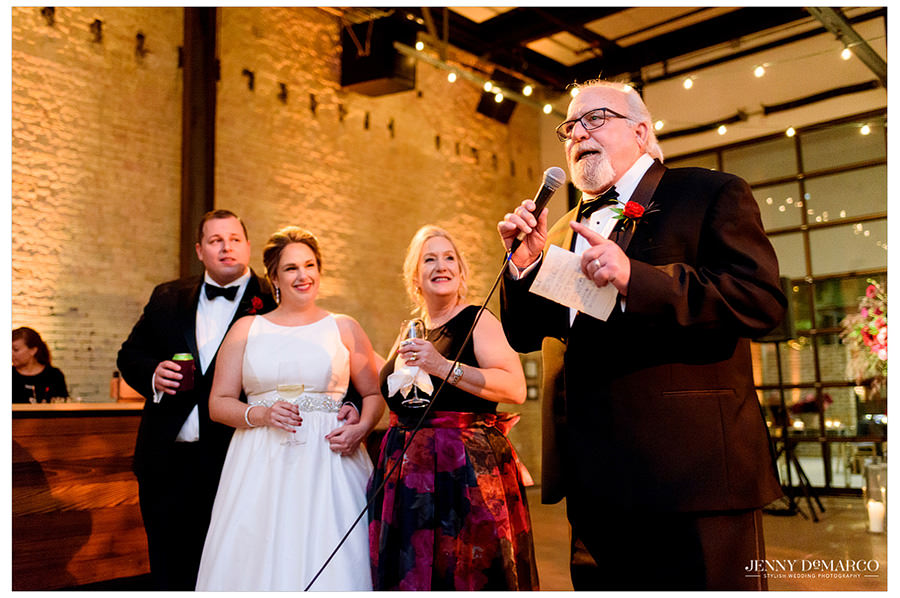 The father of the bride tells a joke during his toast to the happy couple as they all laugh.
