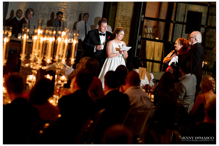 The bride and groom give a speech to their guests at the reception.