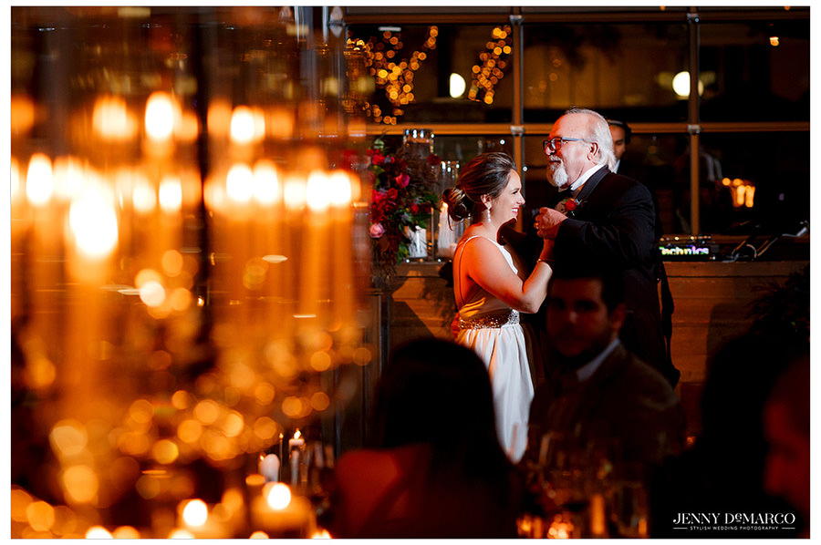 Candles accent the beautiful moment shared by the father of the bride and his daughter as they dance their father daughter dance.