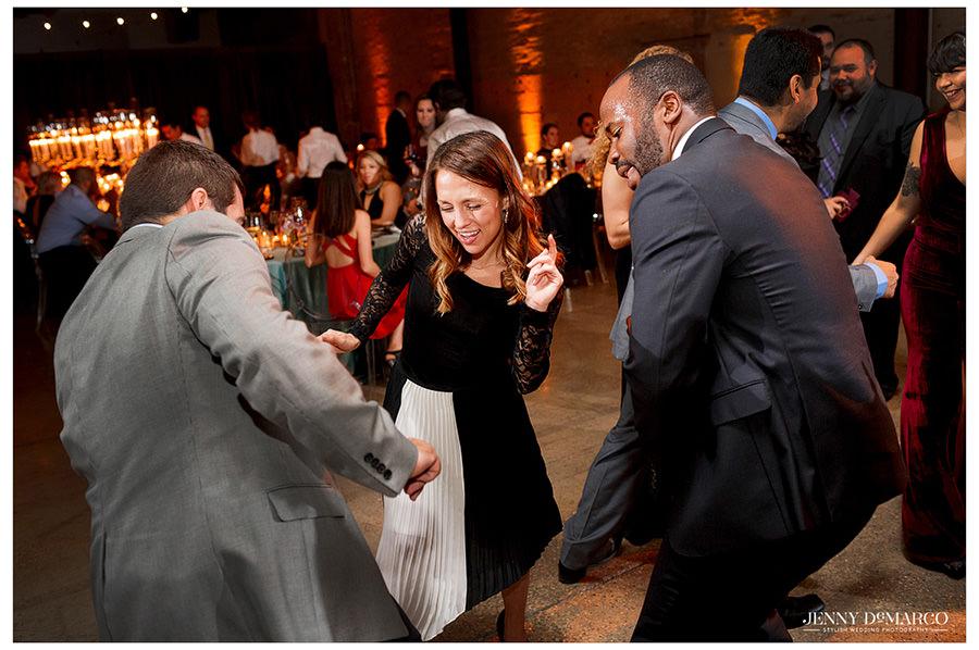 Wedding guests have fun showing off their dance moves as music plays for all to enjoy.