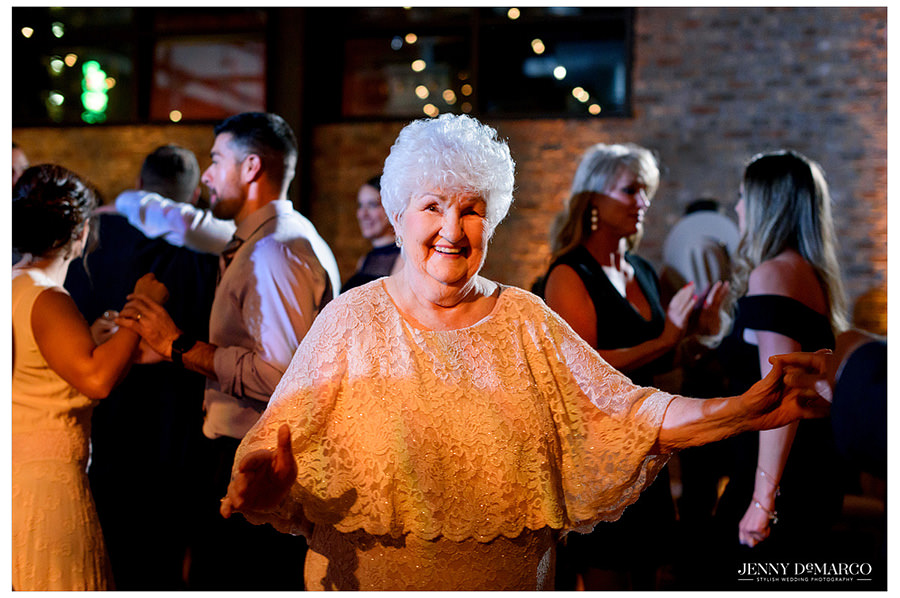 An image of an elderly woman dancing at the reception in an elegant lace dress.