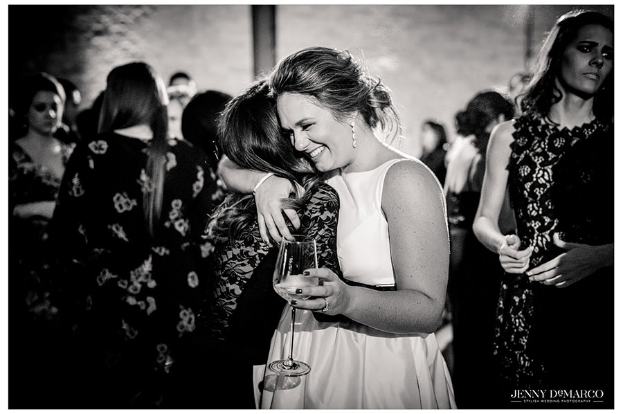 A black and white image of the bride hugging her best friend as her wedding night comes to an end. A sweet candid moment captured by Jenny DeMarco