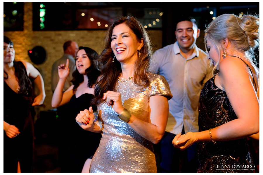 A wedding guest is caught dancing the night away in a gold sequin dress.