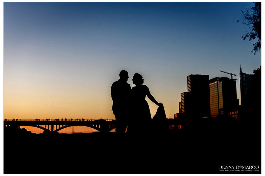A silhouette image of the bride and groom as the sunsets in Austin Texas on Town Lake. The sun highlights the bridge in the background.