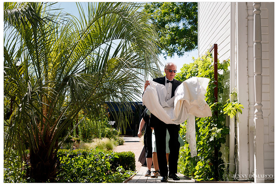 a beautiful shot of the father of the bride bringing in her dress