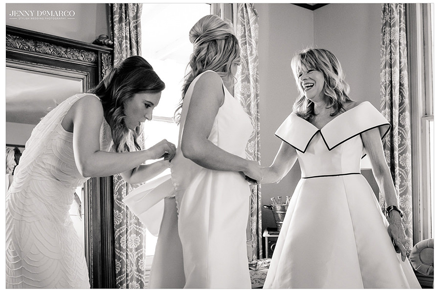 the brides sister helps to button up her one of a kind gown