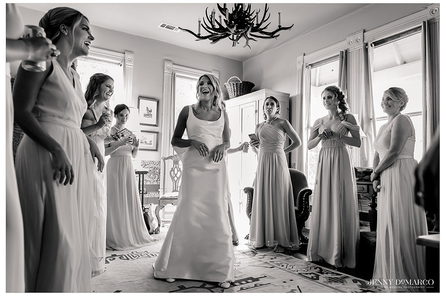 the bridesmaids surround their friend in excitement