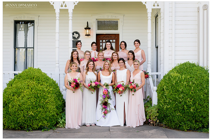 the bride and her stunning bridesmaids pose for a beautiful shot in front of the barr mansion