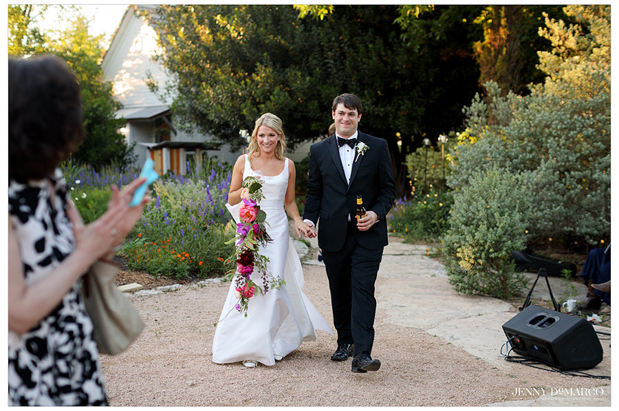 the bride and groom arrive at the reception in austin