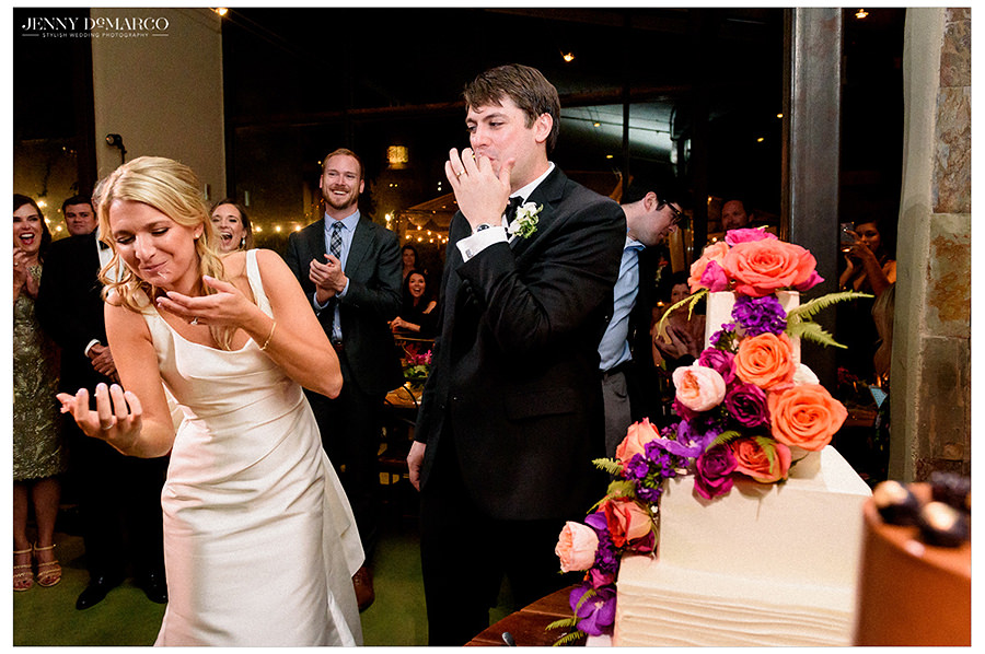 the bride and groom share cake at the reception
