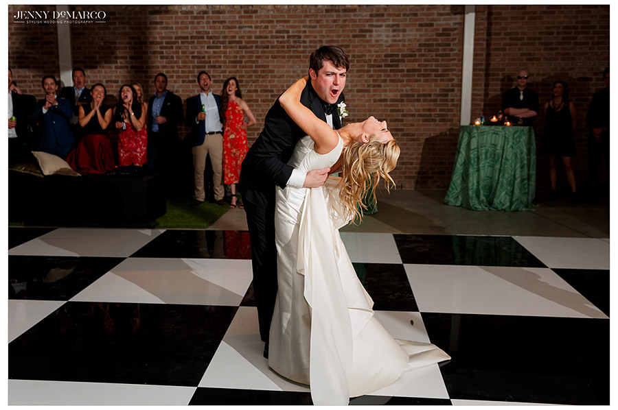 the groom dips her in a playful and sweet first dance