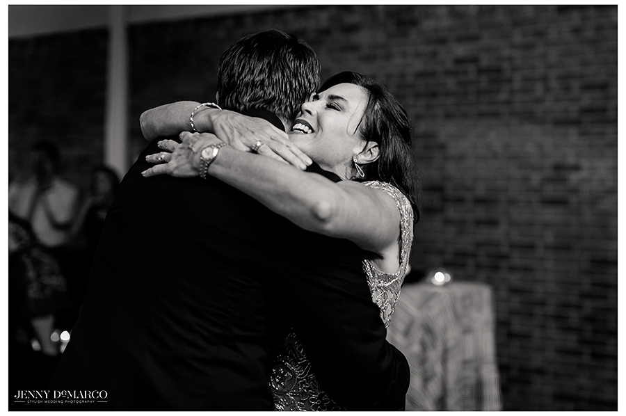 the mother and groom hug in the ballroom of the barr mansion