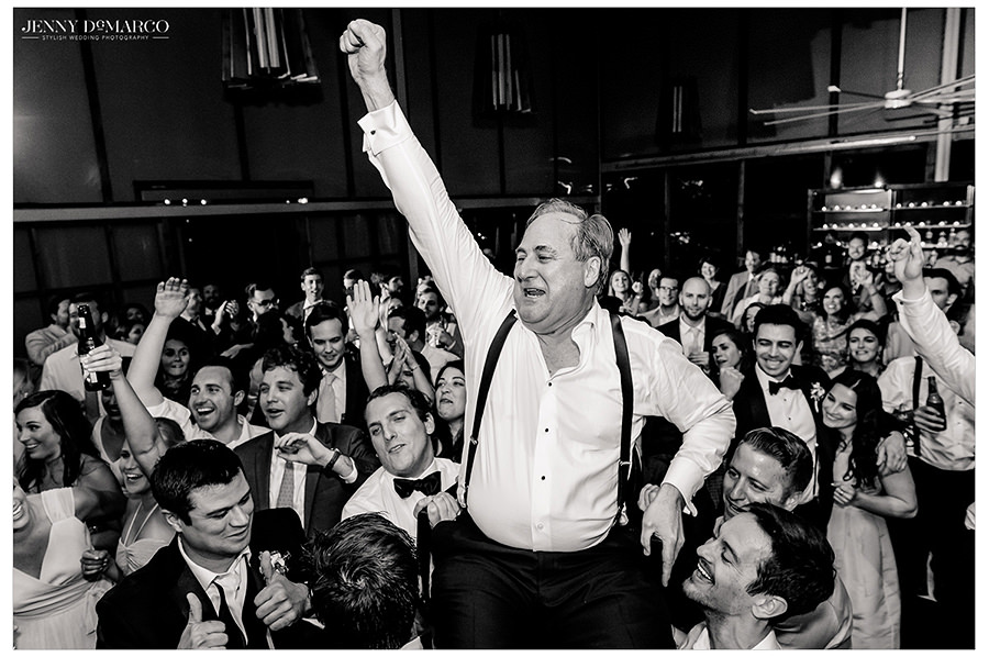 the grooms father is dancing around in the black and white wedding shot