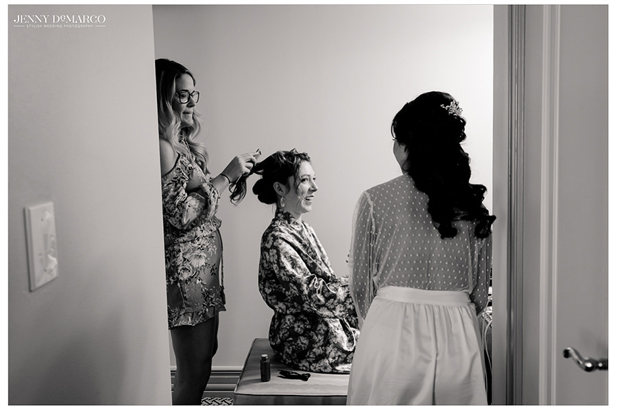 bridal party laughing and getting hair done with bride