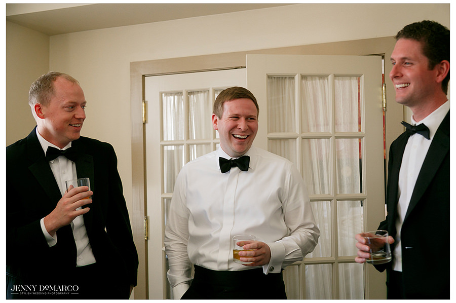 the groom stands laughing with his groomsmen