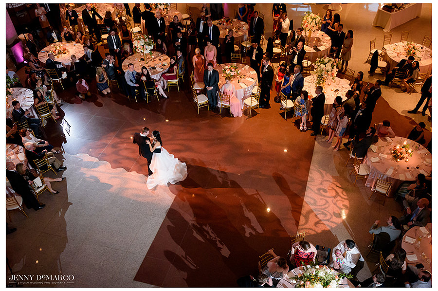 the bride and groom share their first dance in the ballroom of the Bob Bullock museum