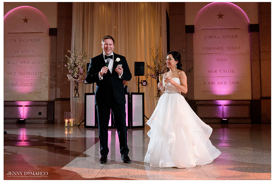 the bride and groom stand in the historic Bob Bullock Museum and cheers