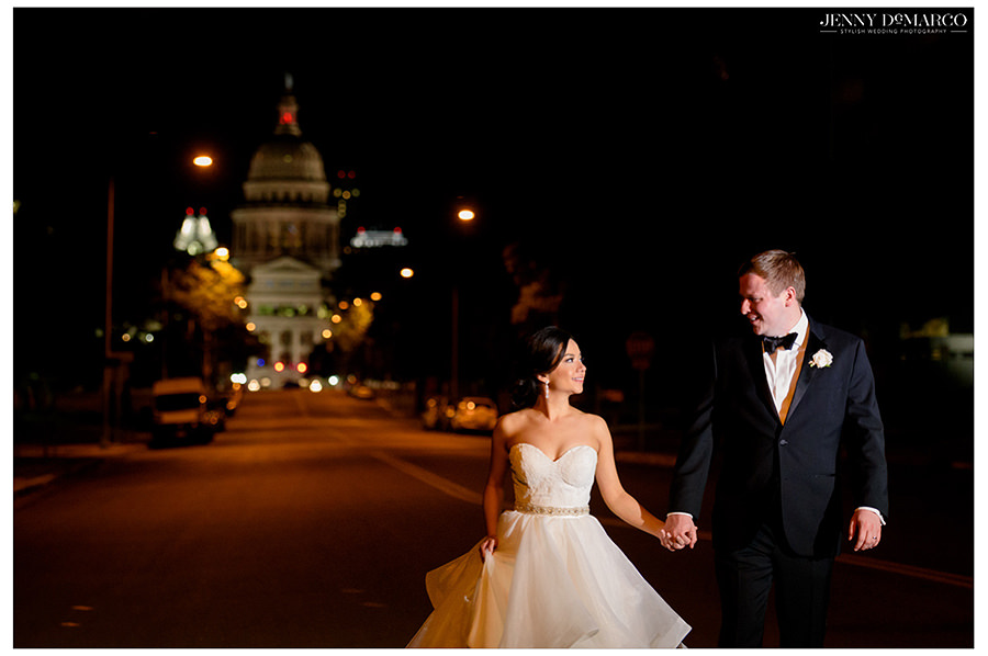 the couple struts down the street with the Texas Capitol in the background