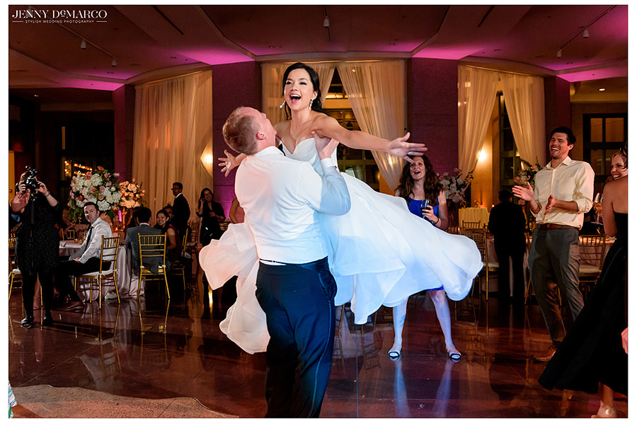 the bride is lifted into the air at the reception