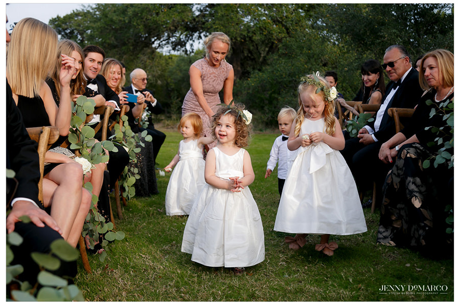 beautiful flower girls walk down isle in the heart of the hill country