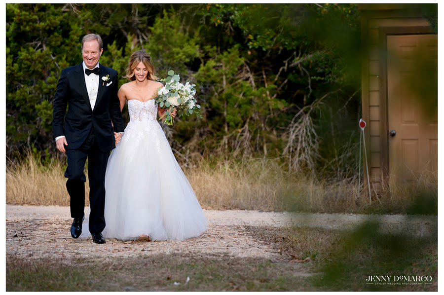 bride and father walk down isle at the Greenhouse at Driftwood