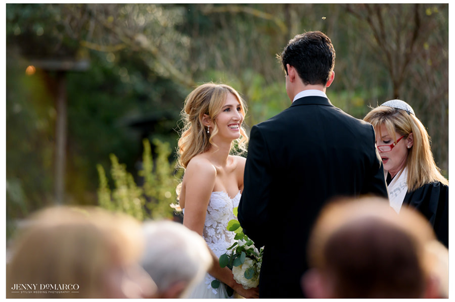 bride looks joyfully of groom while they exchange vows in the beautiful hill country