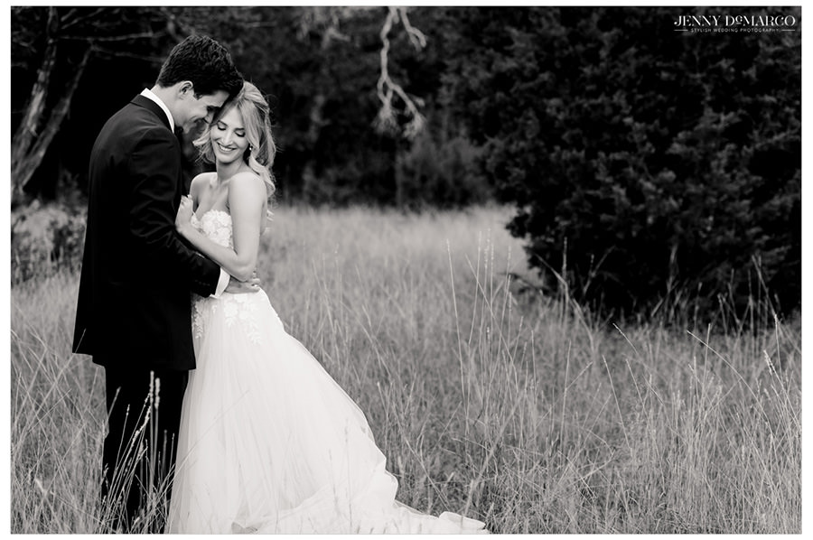 surrounded by nature, the bride and groom share a touching moment in the heart of the hill country