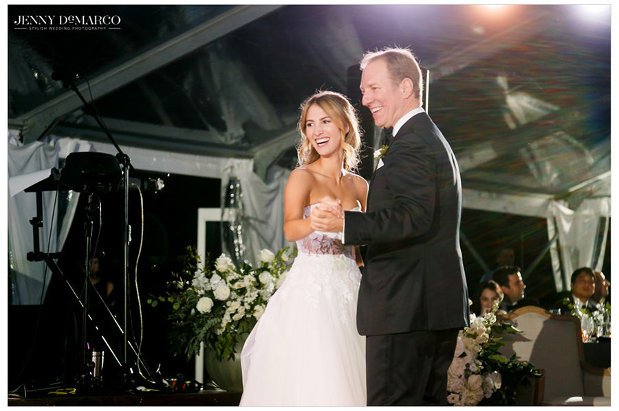 the bride and her father share first dance in the elegant greenhouse