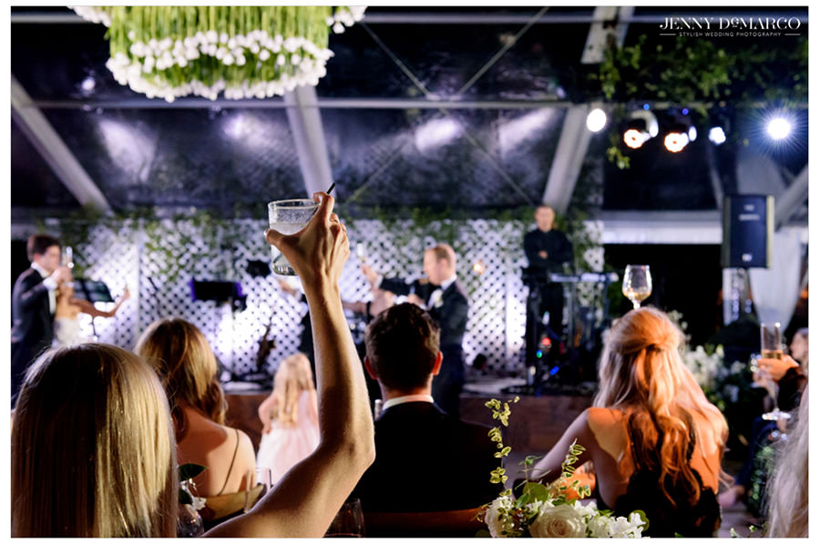 a glass is raised to celebrate the beautiful bride and groom at the Greenhouse at Driftwood