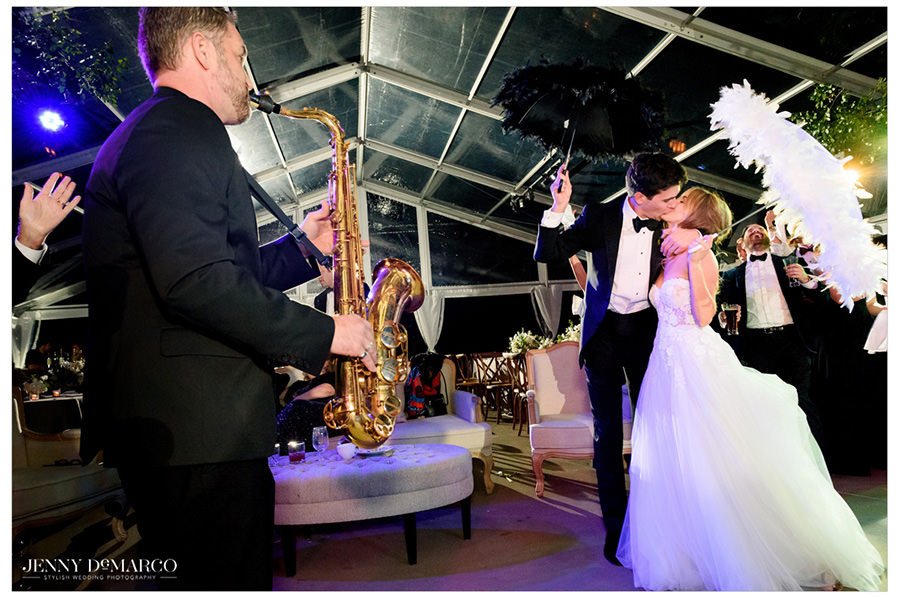 bride and groom share a sweet kiss under feathered umbrellas