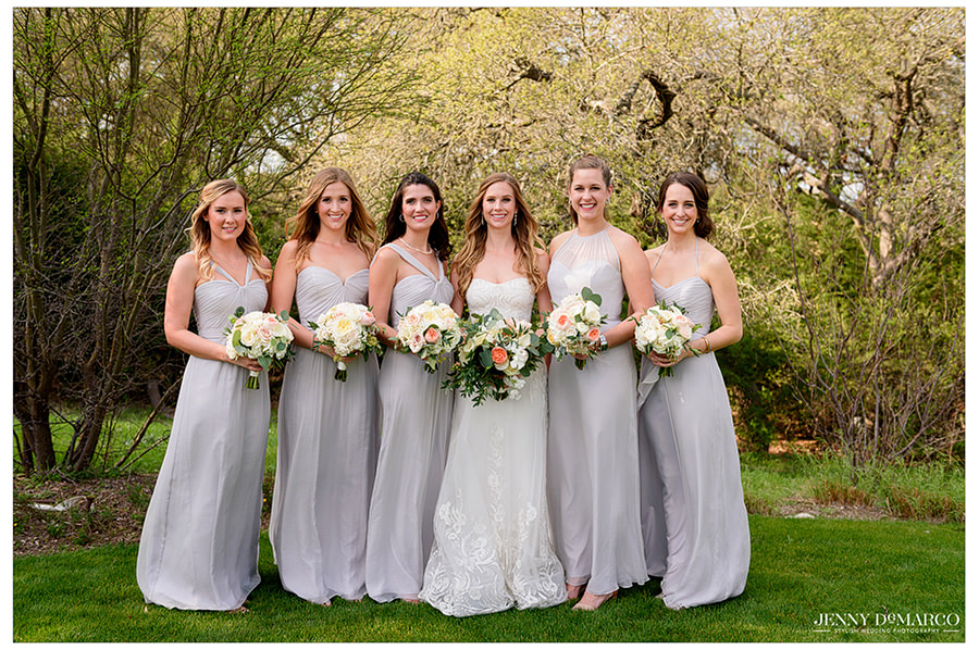 the bridesmaids in grey dresses around the bride