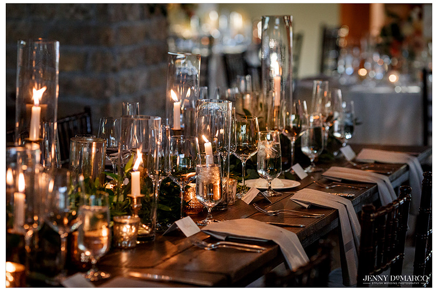 the lighted table and glass details of the reception