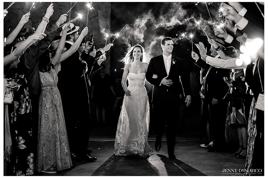 the couple leaves as they enter through a sparker lit pathway to leave