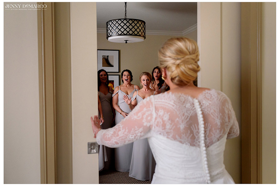 the bride reveals her beautiful lace dress to her bridesmaids