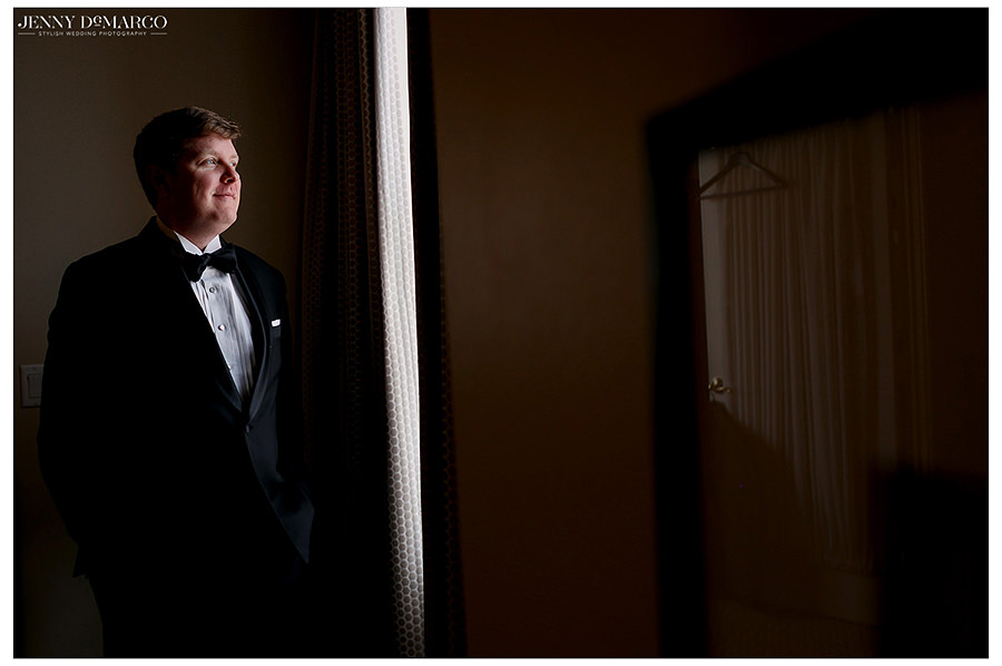 shot in the window of the groom in a black tux