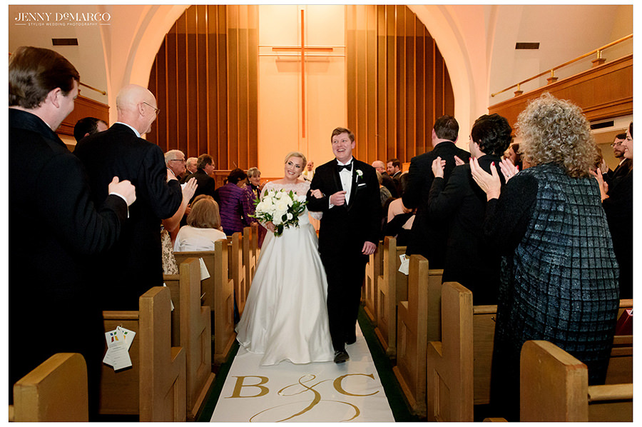 the bride and groom walking out on a beautiful white monogrammed carpet