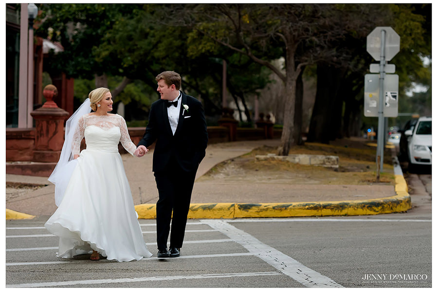 a sweet shot of the bride and groom as they walk down the crosswalk